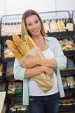 un pain de achat de femme dans l'étagère de pâtisseries Photo stock