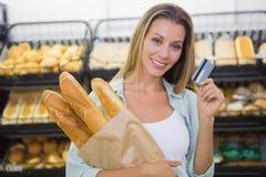un pain de achat de femme dans l'étagère de pâtisseries Photos libres de droits