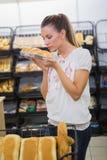 Un pain sentant de femme dans l'étagère de pâtisseries Photos libres de droits