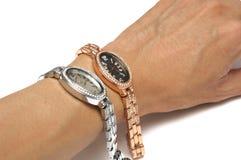 Un paio degli orologi di signore dell'oro e dell'argento con un fronte rotondo dell'orologio sopra un polso del ` s degli uomini Fotografie Stock
