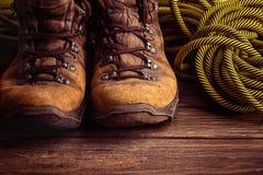 Un paio degli stivali consumati marroni e una corda di sport su un fondo di legno Fuoco selettivo Concetto del viaggio e dell'avv fotografie stock
