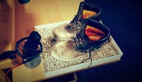 Un paio degli stivali e di un microfono immagini stock
