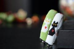 Un paio dei braccialetti in rilievo con un gatto in bianco e nero ed i cuori Immagine Stock