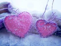 Un paio dei cuori rosa di feltro sulla neve fotografie stock