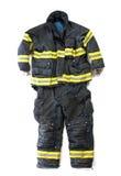 Un paio dei pantaloni e del vestito del pompiere su fondo bianco Fotografia Stock