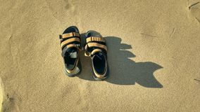 Un paio dei sandali sulla sabbia fotografie stock libere da diritti