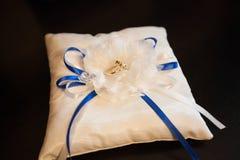 Un paio delle fedi nuziali su un cuscino bianco immagine stock libera da diritti