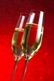 Un paio delle flauto del fondo astratto rosso del champagne Fotografia Stock