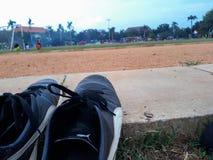 un paio delle scarpe da corsa nere su esposizione sul campo di calcio immagini stock libere da diritti