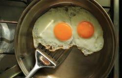 Un paio delle uova del pollo fritto in una padella pronta per il servizio immagini stock