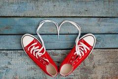 Un paio di retro scarpe da tennis rosse su un fondo di legno blu, pizzi Immagini Stock Libere da Diritti