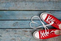 Un paio di retro scarpe da tennis rosse su un fondo di legno blu, pizzi Immagine Stock