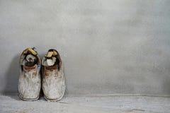 Un paio di vecchie scarpe sul fondo del cemento, vecchio fondo, vecchi stivali Immagini Stock Libere da Diritti