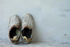 Un paio di vecchie scarpe sul fondo del cemento, vecchio fondo, vecchi stivali Fotografia Stock Libera da Diritti