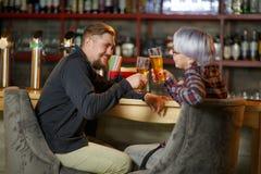 Un paio si siede in una barra ed in acclamazioni con i vetri della birra all'interno Fotografie Stock