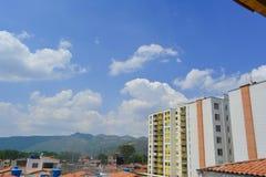 Un paisaje de algunas casas vistas del tejado y de la pared amarilla del edificio con un cielo azul en el fondo imagenes de archivo