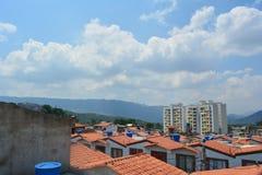 Un paisaje de algunas casas vistas del tejado y de un muro de cemento con un cielo azul en el fondo Foto de archivo