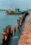 Un paisaje del arasalaru del río con la cerca vieja abandonada del tronco del barco y de la palmera cerca de la playa karaikal fotografía de archivo