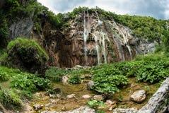 Un paisaje hermoso del verano de las cascadas que caen abajo de las montañas Fotografía de archivo libre de regalías