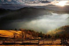 Un paisaje impresionante de la montaña con el sol, la niebla, y f Fotos de archivo