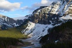 Un paisaje majectic con las montañas nevadas y bosques verdes enormes imagen de archivo