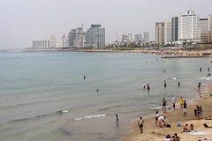 Un paisaje marino de la orilla de la playa por completo de la gente de reclinación fotos de archivo libres de regalías