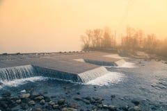 Un paisaje noruego hermoso del otoño Mañana brumosa en un lago Agua que fluye sobre la presa, cascada fotos de archivo