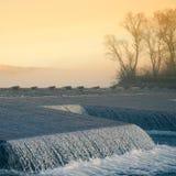 Un paisaje noruego hermoso del otoño Mañana brumosa en un lago Agua que fluye sobre la presa, cascada fotografía de archivo