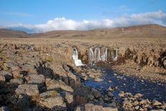 Un paisaje rocoso con una cascada. Fotos de archivo