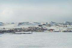 Un paisaje rural con las casas en invierno en la orilla del lago Baikal y las naves en el hielo en un fondo montañoso nevoso Fotografía de archivo libre de regalías