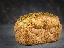 Un pan del pan integral, en la tabla rústica negra Imagen de archivo