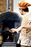 Un pan no identificado de la hornada del hombre en un horno Imagen de archivo