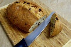 Un pan verde oliva del corte en un tablero con el cuchillo de pan fotografía de archivo libre de regalías