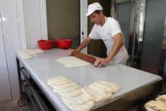 Un panadero amasa la pasta para la empanada del queso con el rodillo y la harina en panadería en la ciudad †de Sofía, Bulgaria  Fotos de archivo