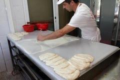 Un panadero amasa la pasta para la empanada del queso con el rodillo y la harina en panadería en la ciudad †de Sofía, Bulgaria  Fotos de archivo libres de regalías