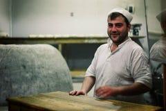 un panadero del hombre en sus clientes que esperan de la panadería para fotos de archivo libres de regalías