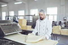 Un panadero hace la pasta en el equipo en la panader?a imagen de archivo