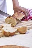 Un panadero que corta un rollo del baguette Fotos de archivo libres de regalías