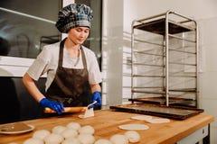 Un panadero que hace los rollos de canela Fotos de archivo libres de regalías