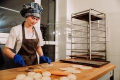 Un panadero que hace los rollos de canela Fotos de archivo