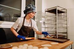 Un panadero que hace los rollos de canela Foto de archivo