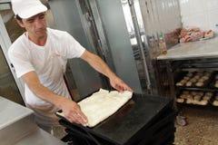 """Un panettiere impasta la pasta per la torta del formaggio con il rullo e la farina in forno nella città †di Sofia, Bulgaria """"4  Immagine Stock Libera da Diritti"""