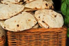 Un panier avec des pains pitas faits maison cuits au four frais et une usine de basilic à la rue cultivent le marché Image stock