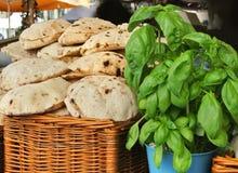 Un panier avec des pains pitas faits maison cuits au four frais et une usine de basilic à la rue cultivent le marché Photos libres de droits