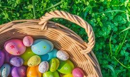 Un panier avec les décorations colorées d'oeufs de pâques sur l'herbe avec des trèfles photo libre de droits