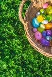 Un panier avec les décorations colorées d'oeufs de pâques sur l'herbe avec des trèfles image libre de droits