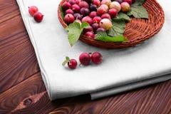 Un panier complètement des groseilles à maquereau rouges savoureuses avec le vert part dans un panier brun clair sur le tissu lég Images libres de droits