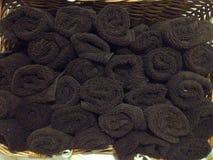Un panier complètement des serviettes roulées de Brown Photographie stock