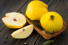 Un panier en osier d'automne jaune de pomme de coing ou de reine porte des fruits, s Photo stock