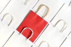 Un panier rojo en el fondo de los bolsos blancos aislados en el fondo blanco Imagenes de archivo